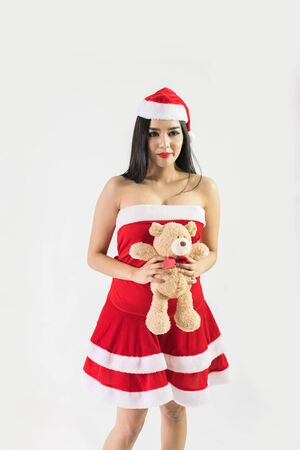 The pretty woman wearing Santa dress on Christmas eve day. Stock Photo