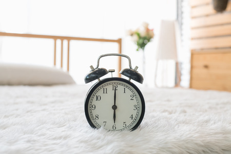 The black alarm clock rings  in the morning in the home. Stock Photo