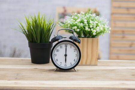 tired: The black alarm clock rings  in the morning in the home. Stock Photo