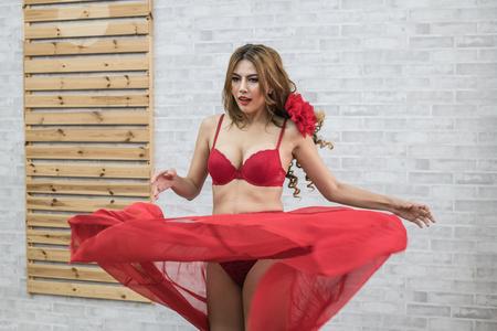 La donna in costume da bagno rosso sexy posa in camera da letto. Archivio Fotografico - 88403722