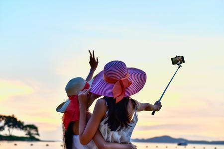 Beautiful girls taking photo on the beach happily.