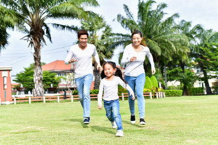 Parents and daughters go for a walk in the park. Happy family concept
