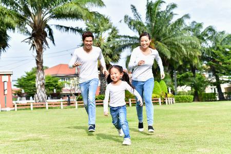 부모와 딸은 공원에서 산책을합니다. 행복한 가족 개념