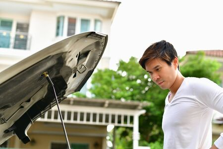Asian man with engine trouble looking at a car with engine cover open.