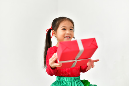 Little girl celebrates Christmas with red Santa dress.