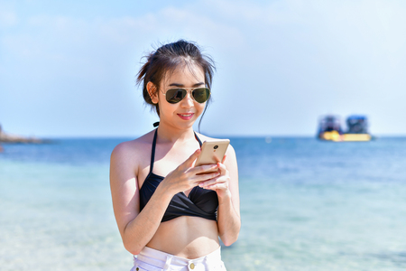Beautiful girl wearing a swimsuit playing mobile on the beach.