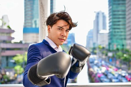 Concept Business people playing sports, business man wearing boxing gloves throwing a punch Stock Photo