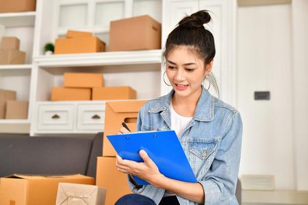 Sme Geschäftskonzept. Junge Asiaten packen ihre Pakete. Auslieferungsunternehmen Small and Medium Enterprise (SMEs). Junger Mann arbeitet im Haus. Junger Inhaber beginnen für Geschäft online.