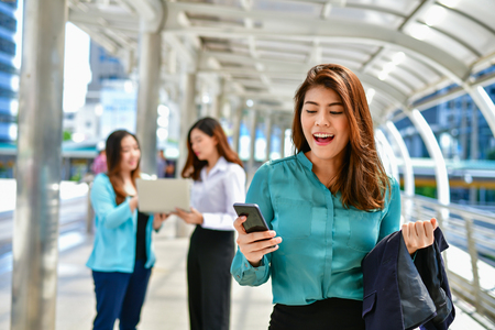 Business Communication Concepts, A young business woman is playing her mobile phone. Stok Fotoğraf