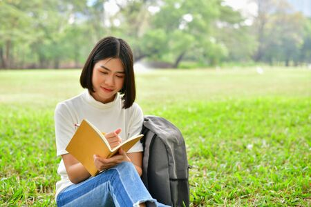 Education Concepts. Asian women reading books in the park. Beautiful women are relaxing in the park. Beautiful women are happy to read. 
