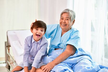 Patient Concept. Grandma's in the hospital. Waiting for someone to visit. Grandchildren visit grandma at the hospital. Grandma is happy to meet grandchildren. 스톡 콘텐츠