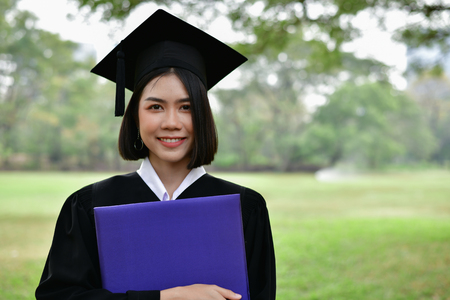 Graduation Concept. Graduated students on graduation day. Asian students are smiling happily on the graduation day. Students wear graduation gowns in the garden 스톡 콘텐츠