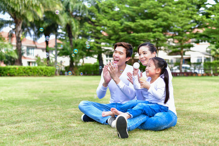 Family Concept. Happy male and female playing with children outside. Family is doing happy activities at Playground.  Parents are playing happily. Stock Photo