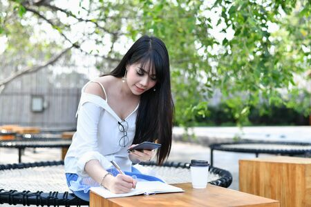 Education Concepts. Asian women reading books in the park. Beautiful women are relaxing in the park. Beautiful women are happy to read. Stock Photo