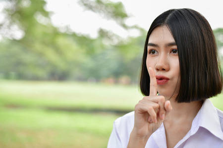 Education Concepts. Beautiful student do not say (silent). Beautiful young students are keeping secret. Beautiful young student is speaking with a soft voice. Stock Photo