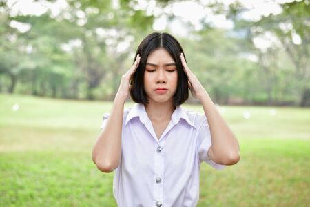 Education Concepts. Beautiful young Asian girl is thinking seriously. Beautiful Asian students are thinking in the garden. Beautiful young student is headache in the garden. Stock Photo