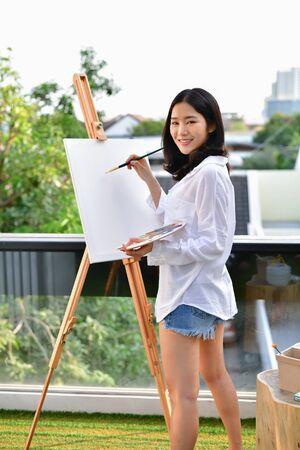 Artista conceptual Hermosa chica. Hermosas mujeres están creando arte. Hermosa mujer está pintando alegremente. Joven artista pintando fuera de la casa.