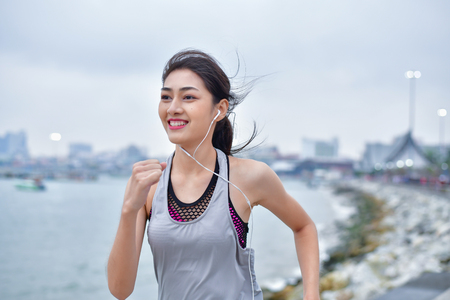Sports concept. Beautiful girl is exercising on the beach with running. Beautiful girl is happy to exercise. Beautiful girls like to exercise by running. People are exercising on the beach. 版權商用圖片