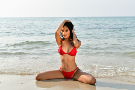 Sexy girl concept in swimsuit. Beautiful woman wearing a swimsuit playing in the beach. Girl in sexy swimsuit poses seductively. Sexy girl seduces a young man on the beach. Standard-Bild