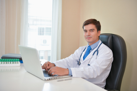 Smiling doctor posing in the office, he is wearing a stethoscope, medical staff on the hospital background