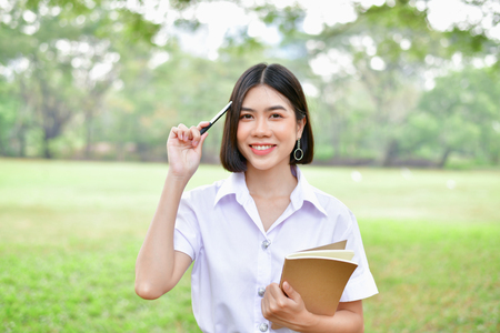 Education Concepts. Beautiful student reading books in the park. Beautiful girl are relaxing in the park. Young student are happy to read. Young student love to study. Education of Asian Women. Stock Photo