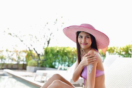 Badpak Concept. Het mooie meisje in zwempak past zonnescherm toe. Mooi meisje in een zwempak beschermt de huid tegen de zon met crème. mooi meisje breng zonnebrandcrème aan op het hele lichaam.