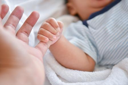 Concepto de recién nacido. Madre e hijo en una cama blanca. Mamá y bebé jugando en el dormitorio. Padre e hijo relajándose en casa. Familia divirtiéndose juntos. El bebé recién nacido se queja y llora.