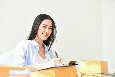 Sme Geschäftskonzept. Junge Leute packen ihre Pakete. Klein- und Mittelunternehmen (KMU). Junge Frau arbeitet im Haus. Junger Inhaber beginnen für Geschäft online.