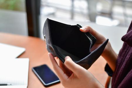 Failliete bedrijfsconcepten. Mooie zakenvrouw was geschokt bij het openen van een portemonnee. Jonge ondernemers hebben geen geld en zijn failliet. Stockfoto