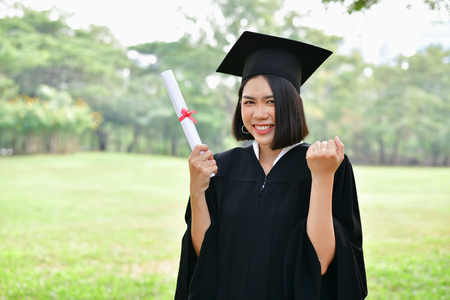 Graduation Concept. Graduated students on graduation day. Asian students are smiling happily on the graduation day. Students wear graduation gowns in the garden Stok Fotoğraf