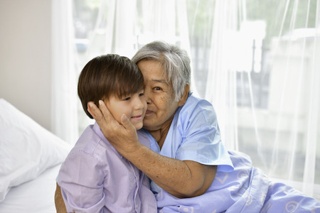 환자 개념. 할머니는 병원에 있어요 누군가 방문하기를 기다리는 중입니다. 손자는 병원에서 할머니를 방문합니다. 할머니는 손자를 만나서 행복합니다.