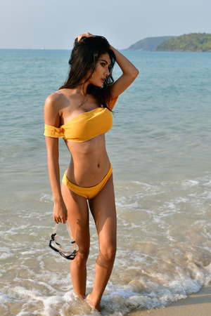 Sexy girl concept in swimsuit. Beautiful woman wearing a swimsuit playing in the beach. Girl in sexy swimsuit poses seductively. Sexy girl seduces a young man on the beach. 스톡 콘텐츠