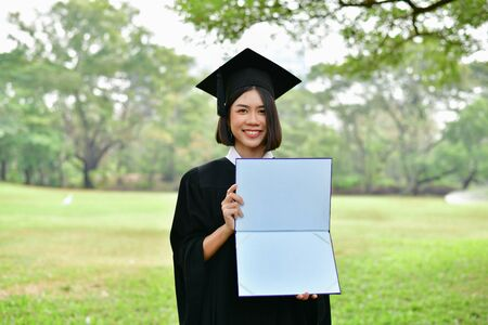 Graduation Concept. Graduated students on graduation day. Asian students are smiling happily on the graduation day. Students wear graduation gowns in the garden Stock Photo