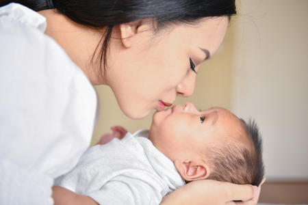 Newborn Concept. Mother and child on a white bed. Mom and baby boy playing in bedroom. Parent and little kid relaxing at home. Family having fun together. Newborn baby is fussing and crying.