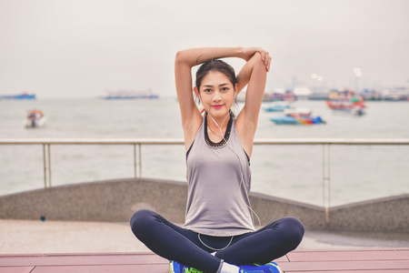 Sports concept. Beautiful girl is exercising on the beach with warm up. Beautiful girl is happy to exercise. Beautiful girls like to exercise by warm up. People are exercising on the beach. Stok Fotoğraf