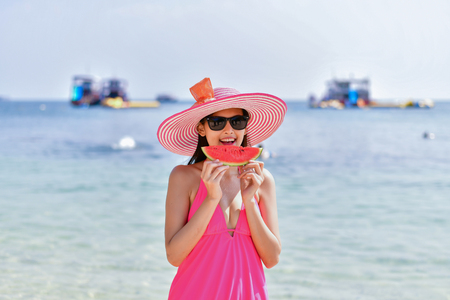 Holiday Concept. Beautiful girl wearing swimsuit eating watermelon beach.  Beautiful girls are enjoying the beach.  Beautiful girl is happy to eat watermelon.