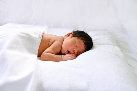 Newborn Concept. Newborn babies are sleeping in a bed. The baby is in the white bedroom.