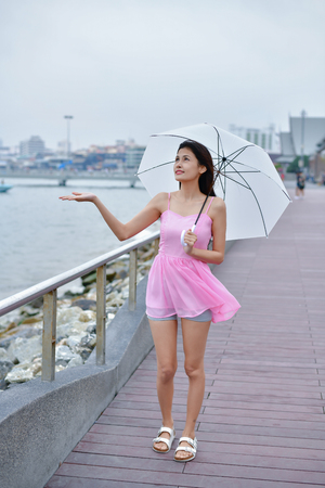 Holiday concept. Beautiful girl is holding umbrella on the beach. Beautiful girl feels cold when it rains. Beautiful girl is smiling happily.
