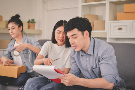 Sme business concept. Young Asian people are packing their packages.Delivery business  Small and Medium Enterprise (SMEs). Young man is working in the house.Young Owner Start up for Business Online.