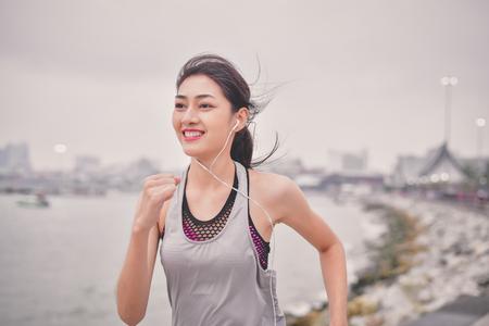 Koncepcja sportu. Piękna dziewczyna ćwiczy na plaży z bieganiem. Piękna dziewczyna chętnie ćwiczy. Piękne dziewczyny lubią ćwiczyć biegając. Ludzie ćwiczą na plaży.