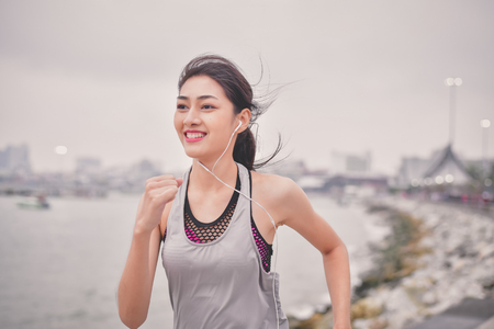Sports concept. Beautiful girl is exercising on the beach with running. Beautiful girl is happy to exercise. 