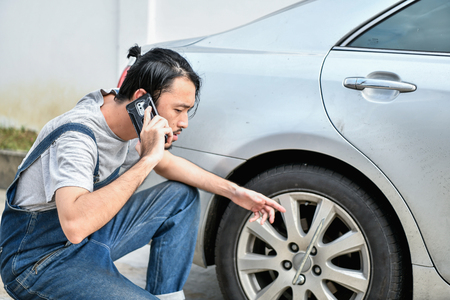 Car Repair Concept. Asian people are repairing cars on the roadside. Asian guy fixes car with confidence Banco de Imagens