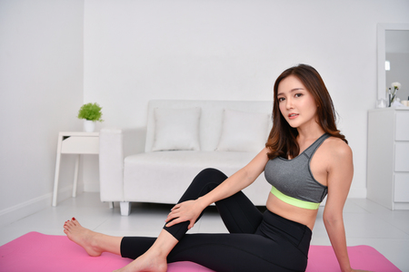 Concept of exercise. Beautiful girl is exercising in her house. Beautiful girl takes good care of her health.