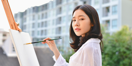Concept Artist Beautiful girl. Beautiful women are creating art. Beautiful woman is painting happily. Young artist painting outside the house. Imagens