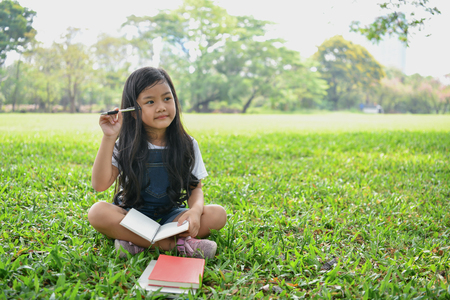 Education Concepts. The girl is reading a book in the garden. Beautiful girl is seriously studying. Beautiful girls are happy learning.