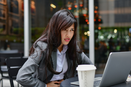 Business Concept. Young businessmen are feeling bad. Young businesswoman is sick. Asian business girl is stressed about her work. Businesswomen are unhappy at work.