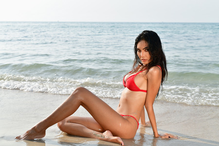 Sexy girl concept in swimsuit. Beautiful woman wearing a swimsuit playing in the beach. Girl in sexy swimsuit poses seductively. Sexy girl seduces a young man on the beach. Stock Photo