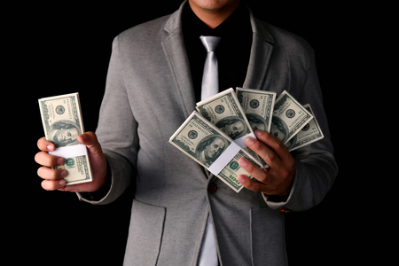 Finance Business Concepts. Lots of money on a black background. Investments are a necessity of business.