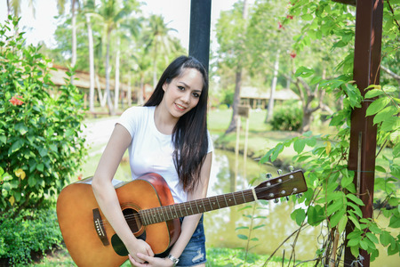 Music Concepts. Asian girls playing guitar. Asian women relaxing with music. Asian women have a happy lifestyle. Beautiful Asian girl playing guitar in the garden.