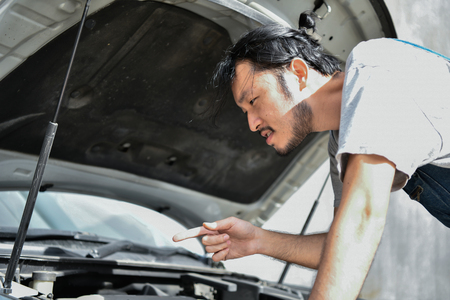 Car Repair Concept. Asian people are repairing cars on the roadside. Asian guy fixes car with confidence 版權商用圖片